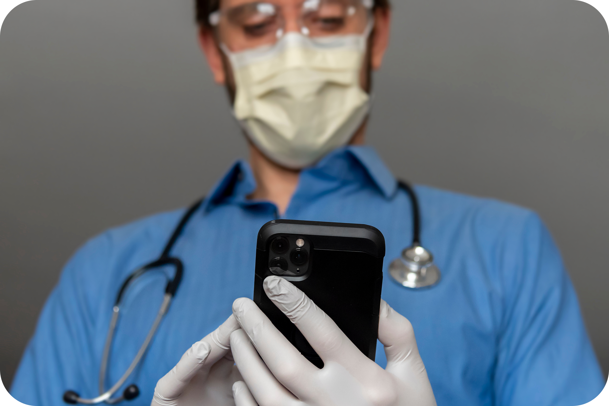 Resident holding mobile phone reviewing surgical training